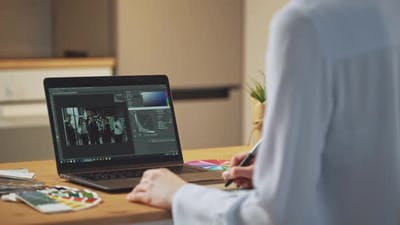 Woman Photo Editor Processes Office Photos on a Laptop at Home Freelancer at Remote Work in
