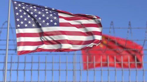Waving Flags of the USA and China Separated By Barbed Wire
