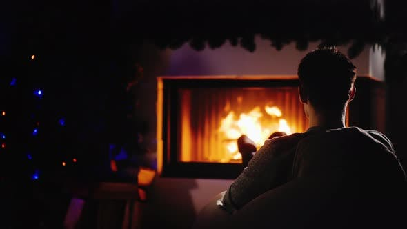 Thumbnail for Young Confident Man Resting By the Fireplace and Christmas Tree