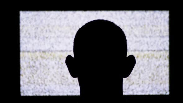 Silhouette of a Man's Head in Front of White Noise and TV Interference.