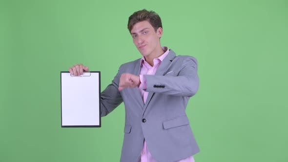 Thumbnail for Stressed Young Businessman Showing Clipboard and Giving Thumbs Down