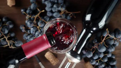 Red Wine Is Poured Into the Glass. Top View. On a Wooden Background