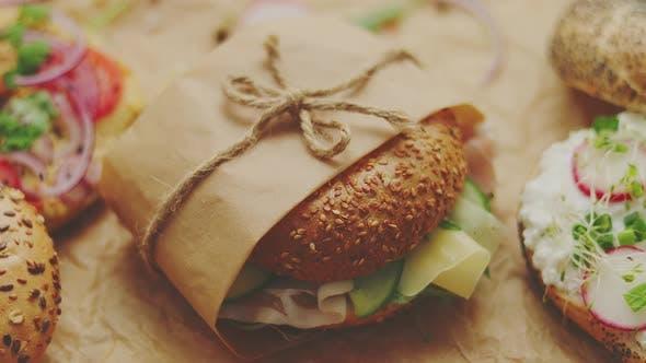 Thumbnail for Bagels mit Schinken, Frischkäse, Hummus, Rettich eingewickelt in braunem Backpapier zum Mitnehmen