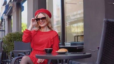 Young Woman Smiles and Adjusts Stylish Sunglasses