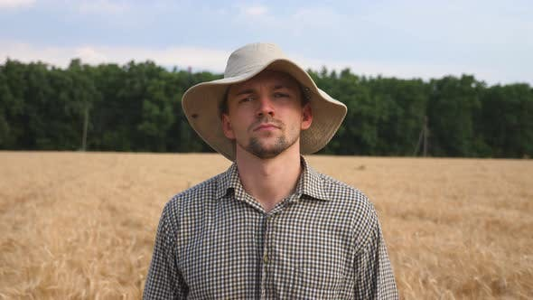 Thumbnail for Portrait of Serious Farmer in Hat Looking Into Camera Against the Blurred Background of Wheat Field