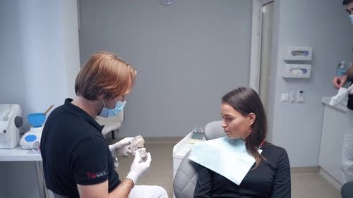 Dentist Showing Jaw Model to a Patient.