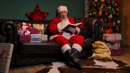 Santa Claus Is Reading a Book with Fairy Tales