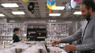 Multiethnic Customers Perusing Merchandise in Record Shop