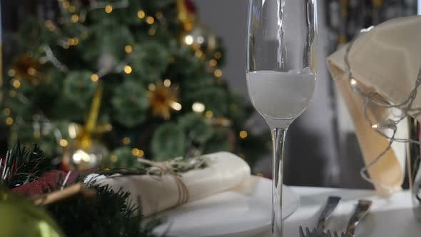 New Year Holiday. Champagne Being Poured Into Glass on Decorated Feast Table and Christmas Tree with