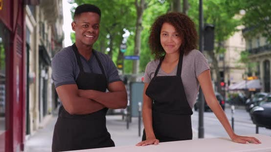 Thumbnail for Portrait of two waiters smiling at camera outside café