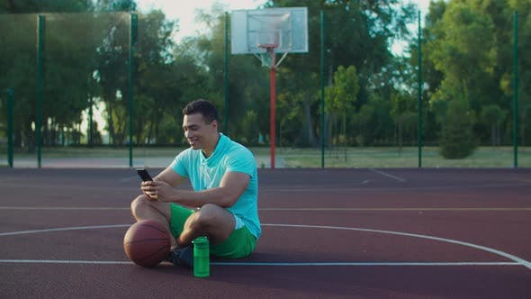 Cover Image for Basketball Player Networking with Phone on Court