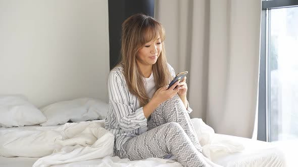Attractive Asian Woman in Stylish Home Clothes Is Sitting on the Bed with a Smartphone in Her Hands