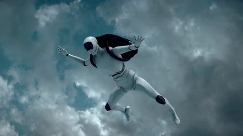 A Autonomus Cyborg Robot Skydiver Is Flying Above White Clouds 4k