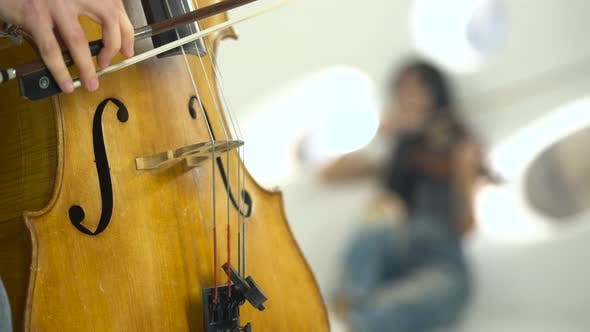 Thumbnail for Closeup of a Playing the Cello in the Background Playing the Violin