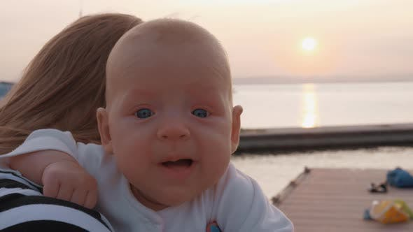 Thumbnail for Baby Girl in Mothers Hands Outdoor at Sunset