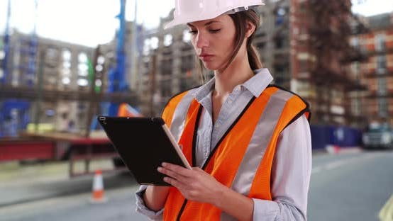 Thumbnail for Focused female construction worker at work on pad device at construction site