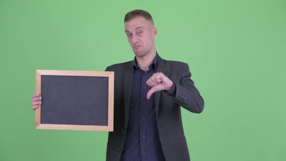Thumbnail for Stressed Businessman in Suit Holding Blackboard Giving Thumbs Down