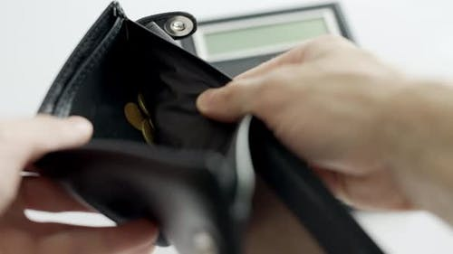 A Man Hands are Opening an Empty Black Wallet in Which Only Coins