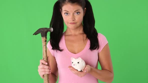 Thumbnail for Portrait of young woman holding a piggy bank and hammer
