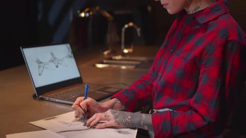 Girl with a Tattoo Draws on Paper. Sliding