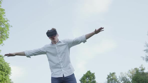Thumbnail for Young Man in Virtual Reality Headset Spread His Arms To the Side, Imitating the Flight of an