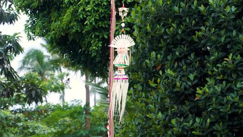 A Traditional Strawy Decoration of Balinese Hinduism Waving in Wind with Palm Trees in the