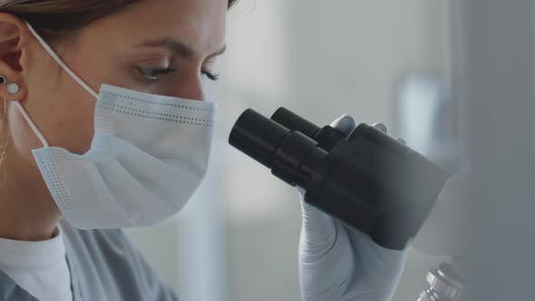 Female Doctor Using Microscope in Lab