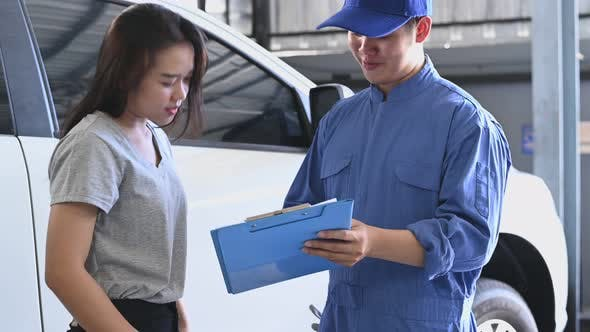 Asian car mechanic and female customer discussing to repairing and maintenance fixing automobile