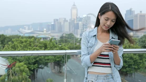 Thumbnail for Woman using mobile phone in city