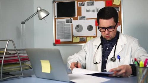 A Young Doctor Signs Documents at the End of the Day in the Private Clinic