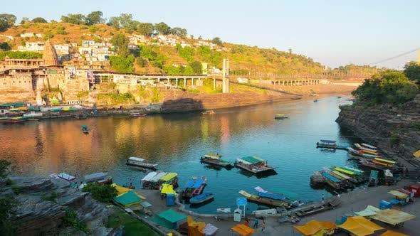 Thumbnail for Time lapse: Omkareshwar cityscape, India, sacred hindu temple. Holy Narmada River, boats floating