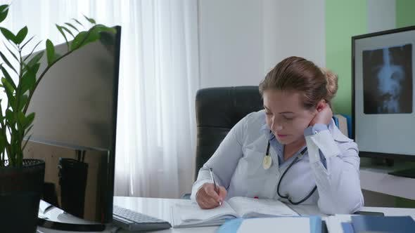 Thumbnail for Sick Woman Doctor Does Not Feel Well Due To a Virus or Infection While Working Sitting at a Table in