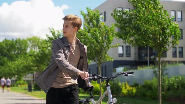 Thumbnail for Young Man with Bicycle Walking Along City Street