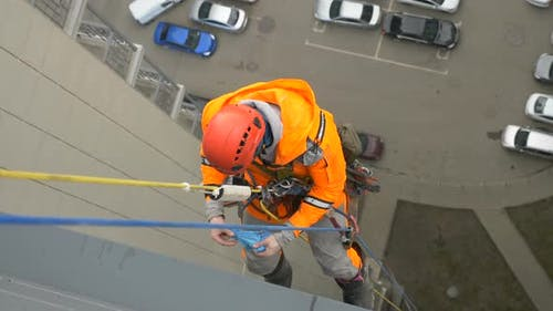 Fighting the Coronavirus Pandemic. Industrial Climber Puts on Rubber Gloves Before Disinfecting the