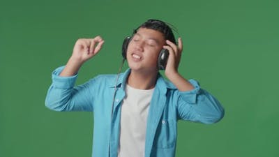 Young Asian Boy Listening To Music With Headphones And Dancing In The Green Screen Studio