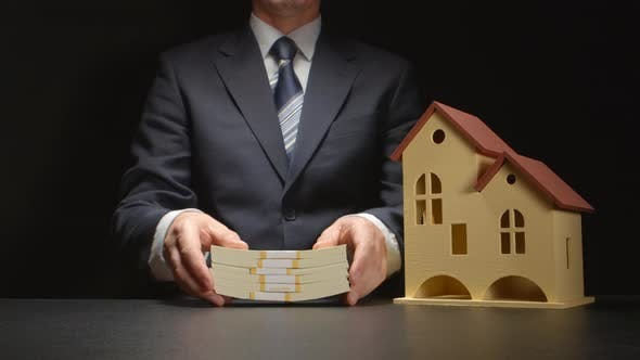 Businessman counts and gives a money and near a house model on a table