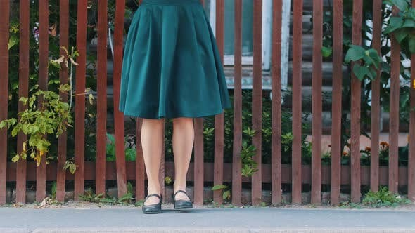 Thumbnail for A Young Slim Woman in Emerald Skirt Dancing Wearing Black Shoes By the Fence