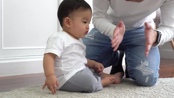 Happy Asian Family of Young Father Playing Games and Clapping Hands with Baby Boy Child at Home