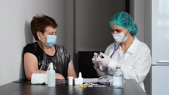 Arzt überprüft Lungen der Frau mit Stethoskop