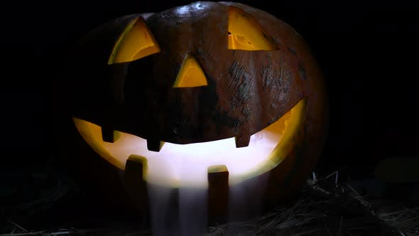 Thumbnail for Helloween Pumpkin Has a Mad Face Also a Smoke in Its Mouth and Teeth. Black Background. Close Up