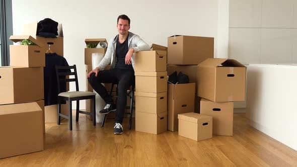 Thumbnail for A Happy Moving Man Sits on a Chair and Smiles at Camera in an Empty Apartment, Surrounded By Boxes