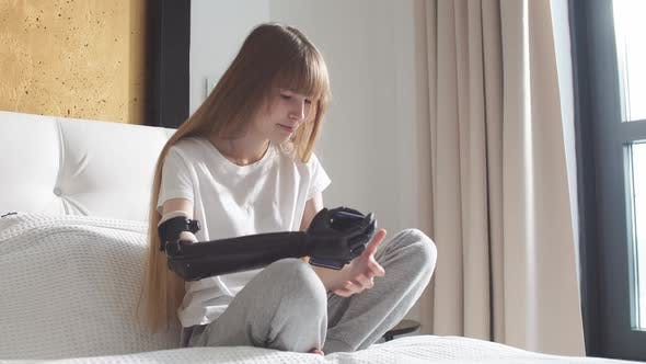 Girl Checking Her Robotic Mechanical Arm Indoors