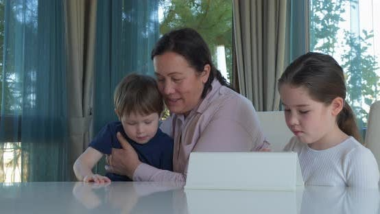 Thumbnail for Grandma Entertaining Her Little Grandchildren with a Tablet Computer Game