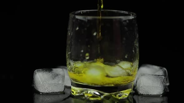 Thumbnail for Whiskey with Ice. Pouring Whisky Rum From the Bottle on Black Background