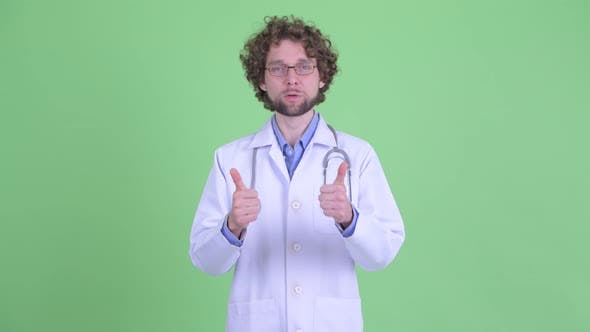 Cover Image for Happy Young Bearded Man Doctor Giving Thumbs Up and Looking Excited