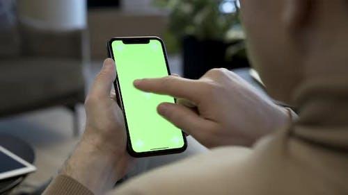 Man Swiping On Smartphone With Green Screen