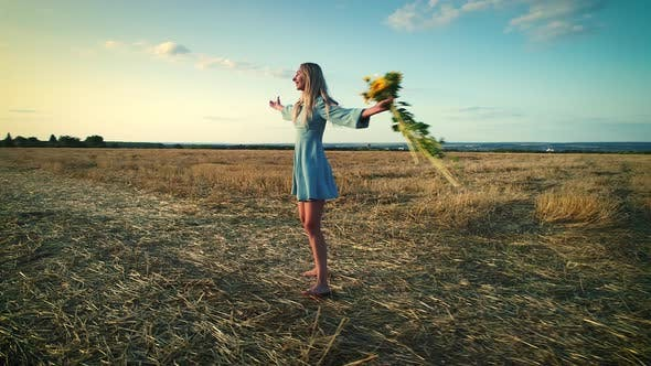 Cover Image for Girl Sniffing Flowers. Young Sunflowers