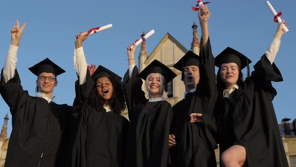 Thumbnail for Happy Group of Students with Arms Up at Their Graduation.