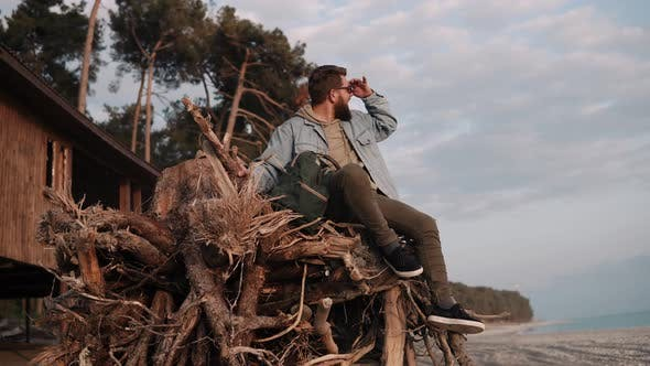 Thumbnail for Young Bearded Man Is Sitting on Wooden Branches on Sand Beach