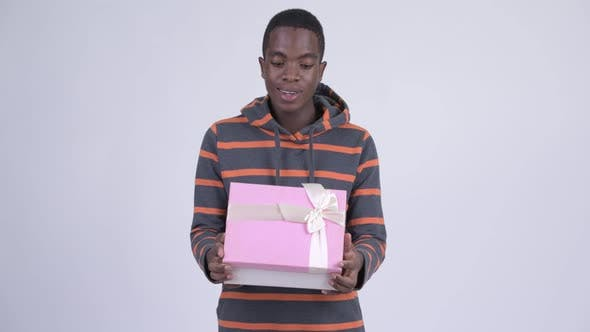 Cover Image for Young Happy African Man Opening Gift Box